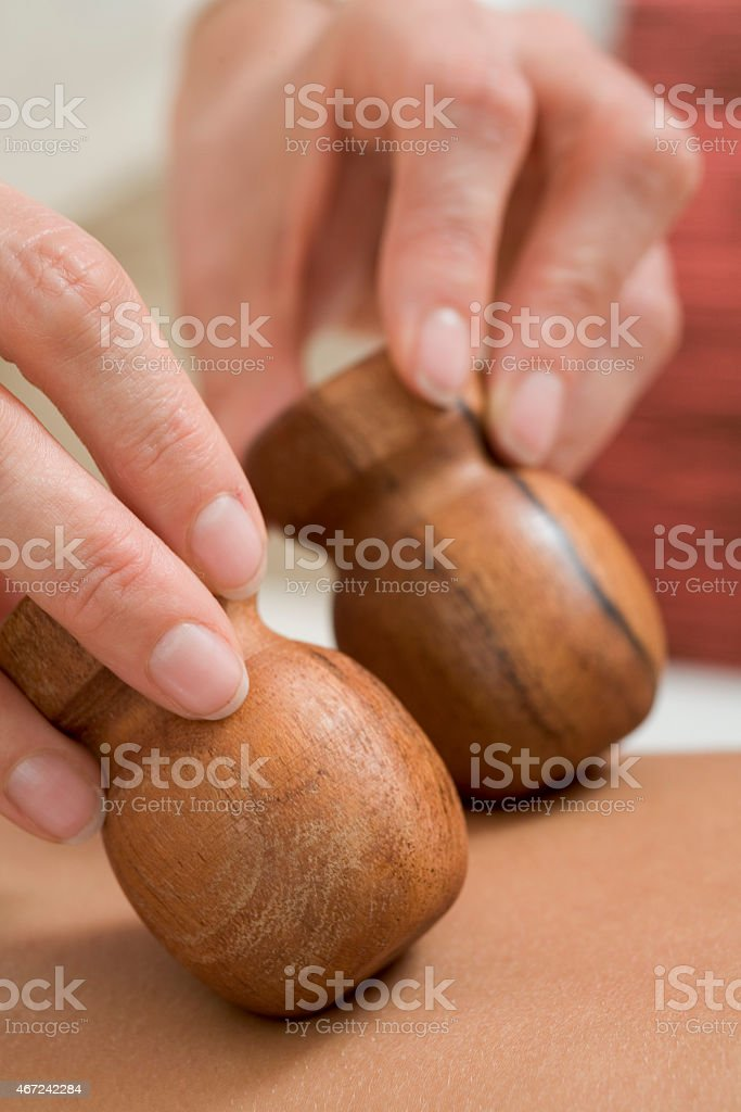 Young woman receiving massage with wooden stamps stock photo