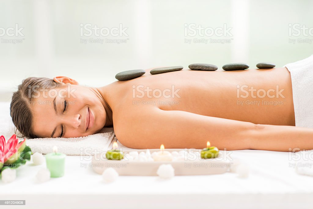 Young woman receiving stone therapy treatment. stock photo