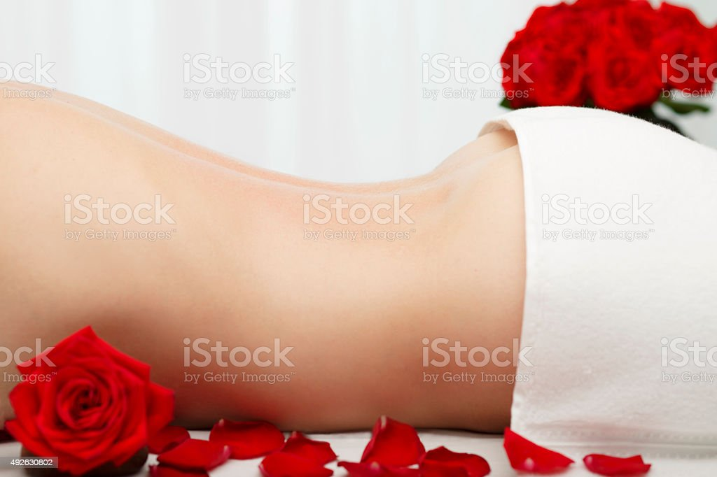 Young Woman Receiving  Swedish Deep Tissue Massage Red Roses stock photo