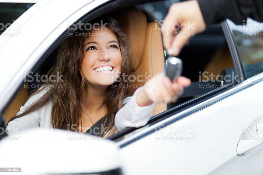 Young woman receiving the keys of her new car stock photo