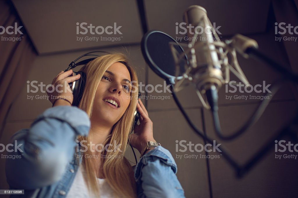 Young woman recording new song in music studio. stock photo
