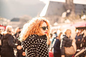 Young woman redhead walking through city