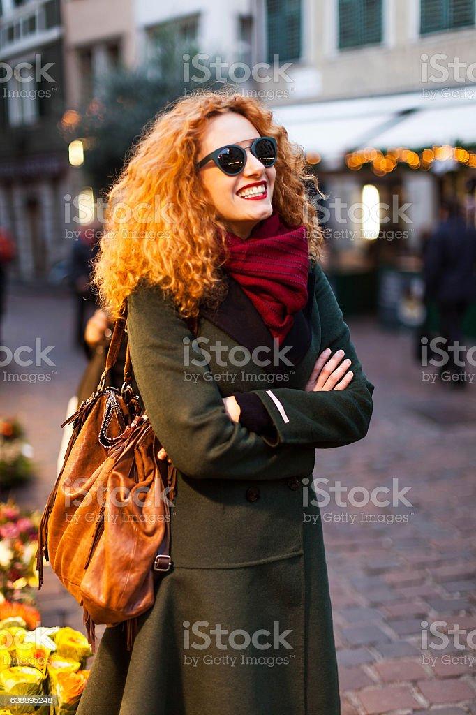 Young woman redhead walking through citylight stock photo
