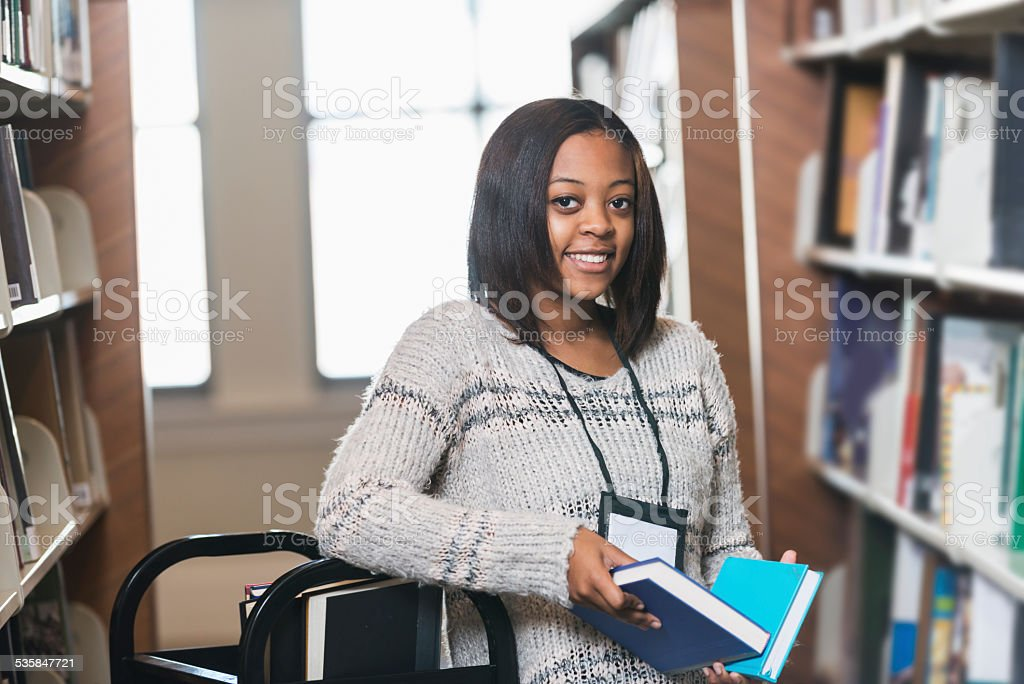 Young woman refiling books on library shelf stock photo