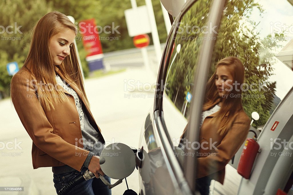 Young woman refilling car with gas pump stock photo