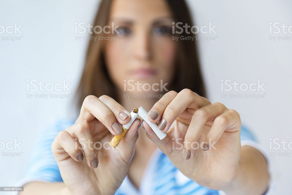 Young woman refuses to smoke and breaks cigarette. stock photo
