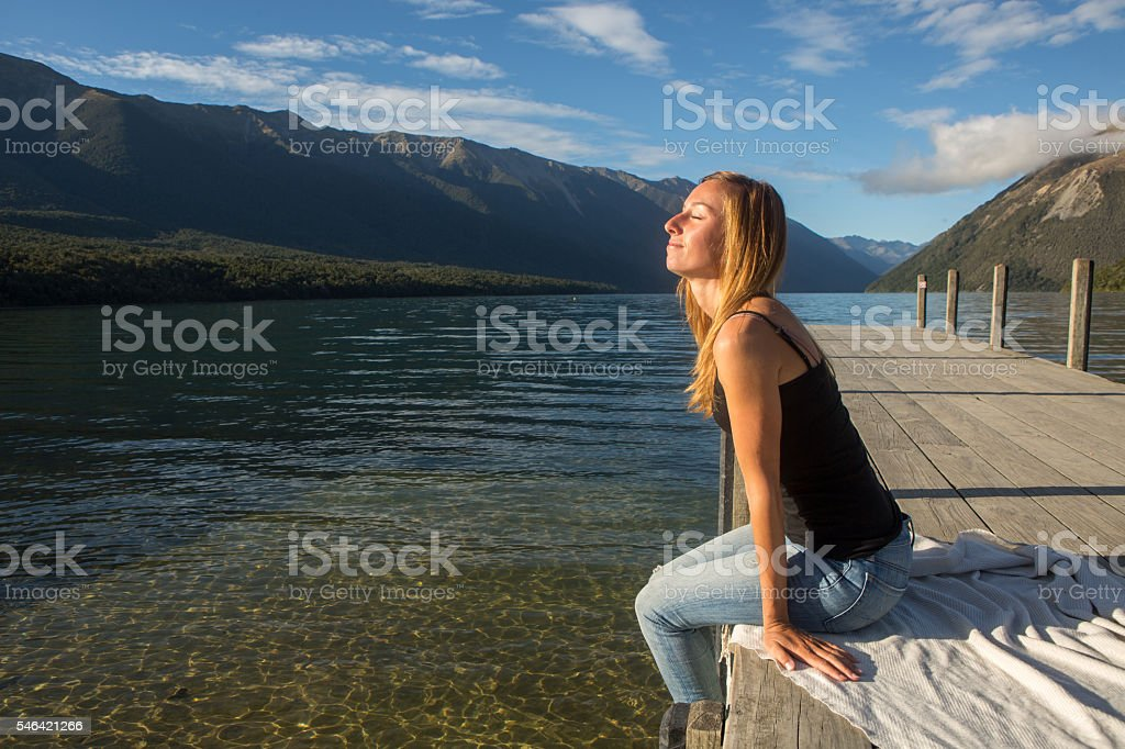 Young woman relaxes on lake pier at sunrise stock photo