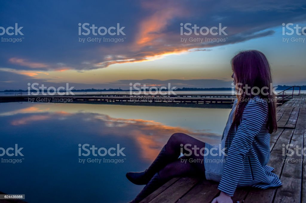 Young woman relaxes on lake pier enjoying moment royalty-free stock photo