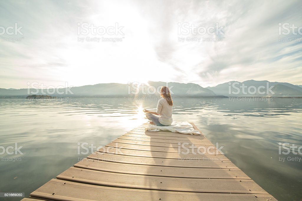 Young woman relaxes on lake pier, exercises yoga stock photo