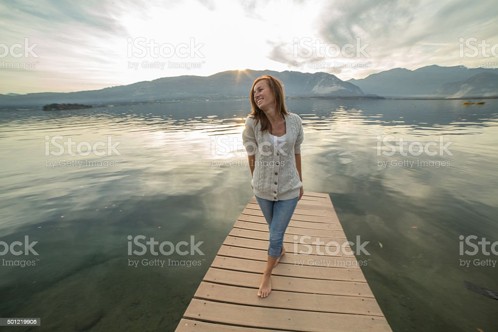 Young woman relaxes on lake pier stock photo