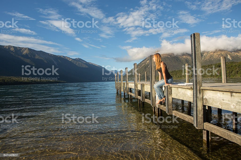 Young woman relaxes on lake pier, sunrise stock photo