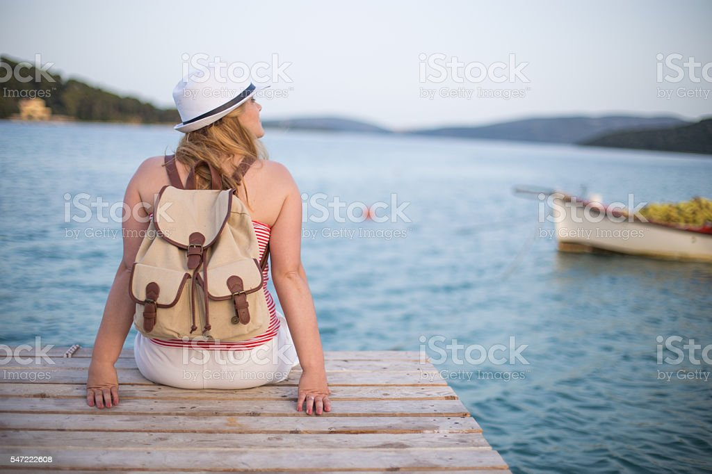 Young woman relaxes on pier stock photo