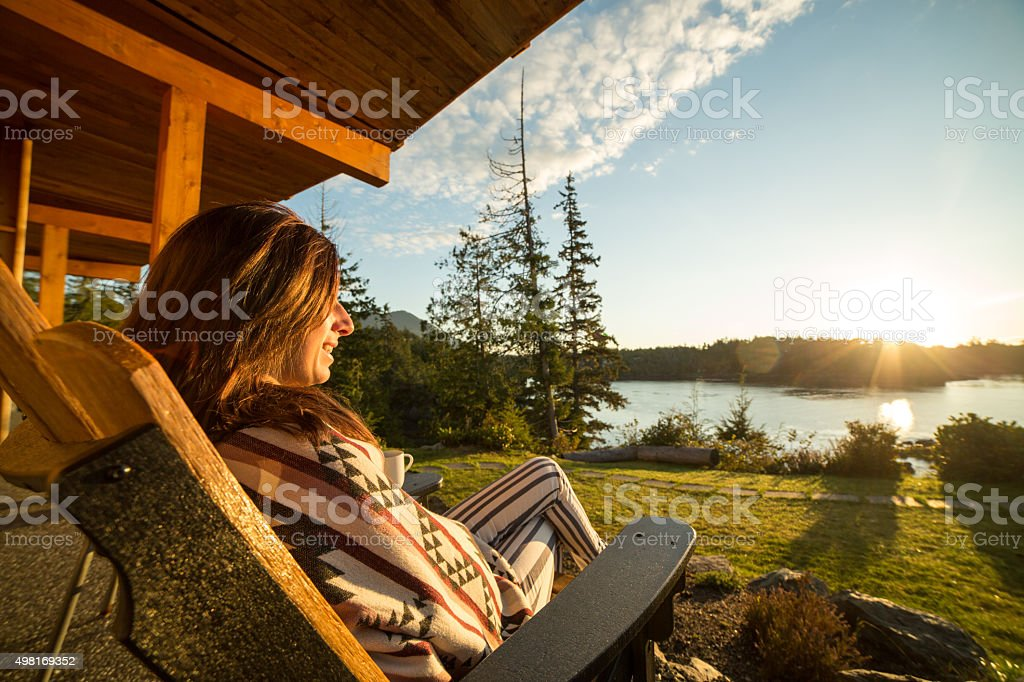 Young woman relaxing and watching sunrise stock photo