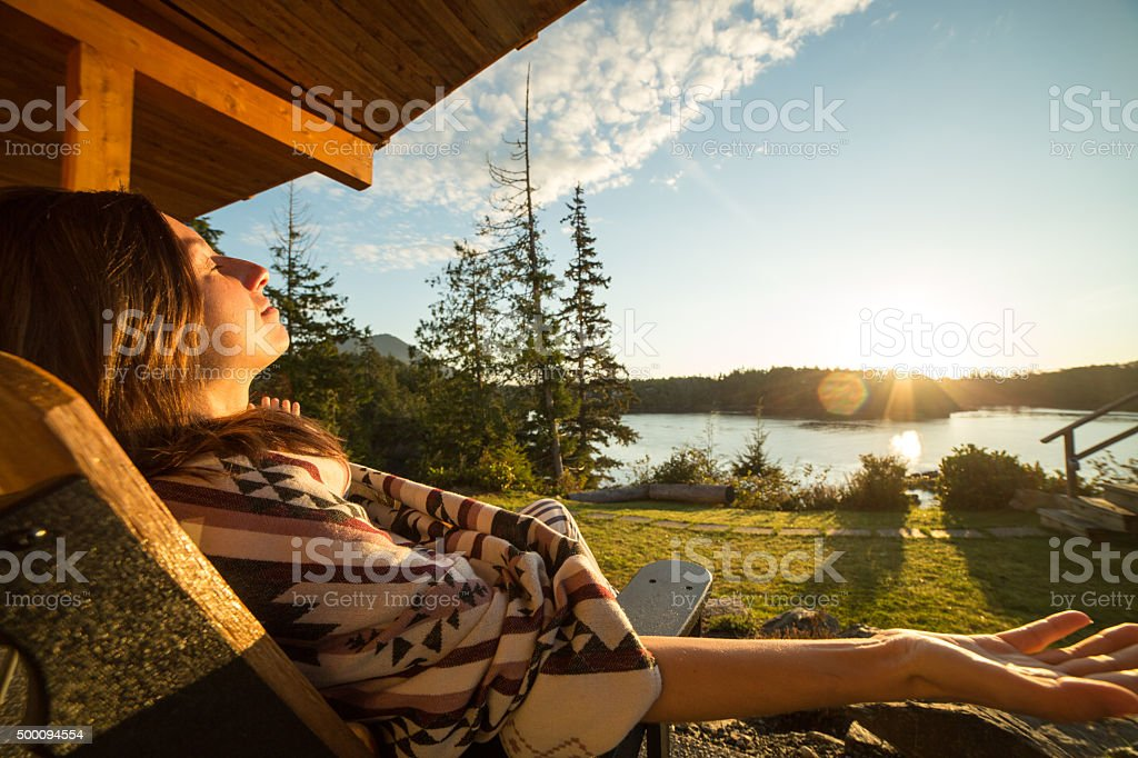 Young woman relaxing at sunrise stock photo