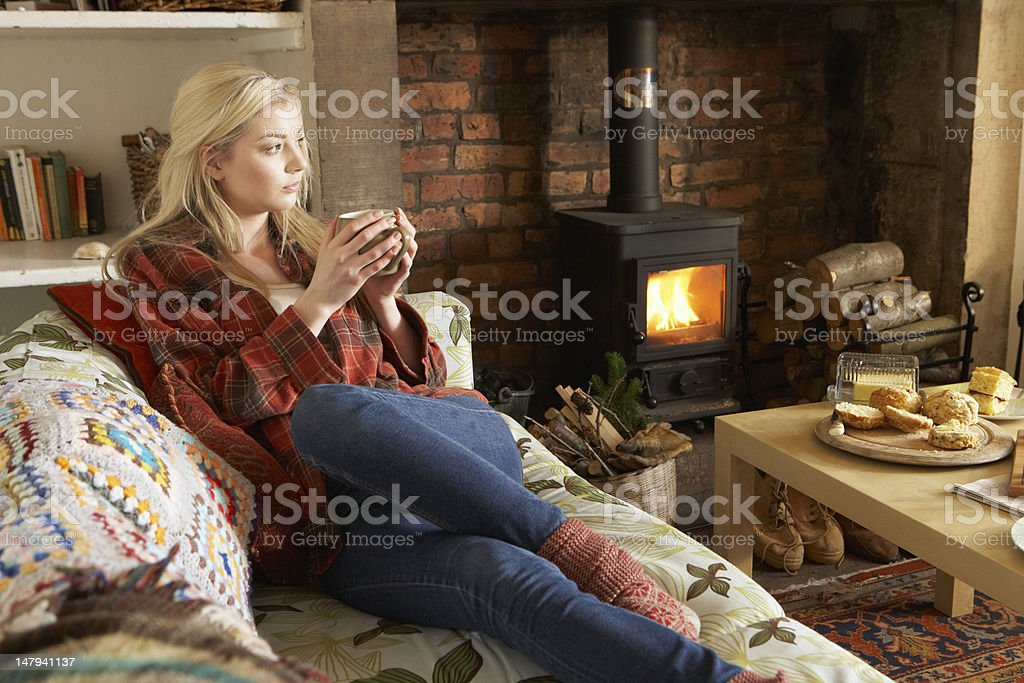 Young woman relaxing by the fire in a cosy living room stock photo