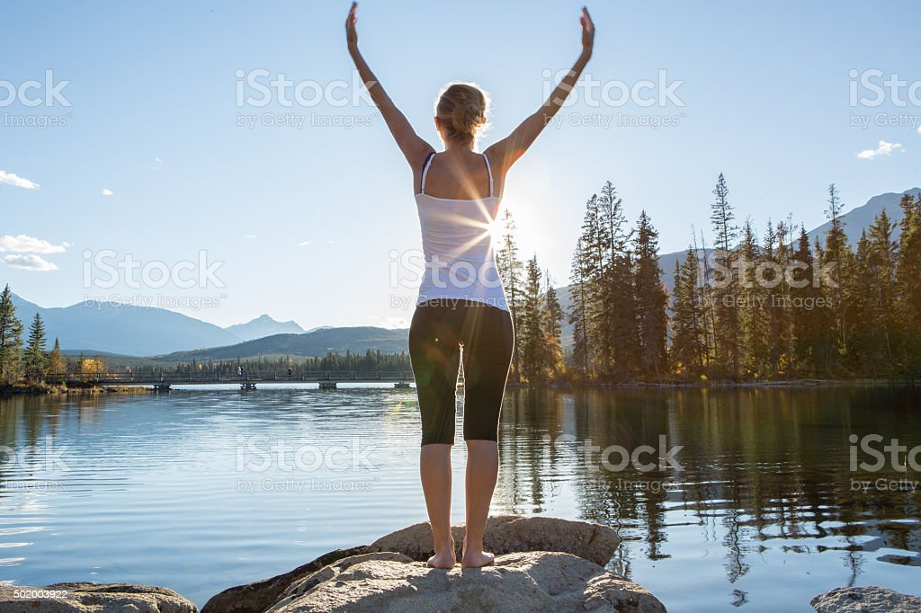 Young woman relaxing by the lake, arms outstreched stock photo
