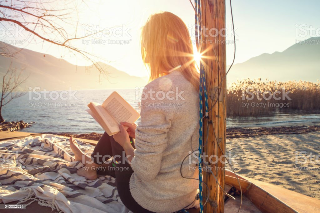 Young woman relaxing by the lake reading book stock photo
