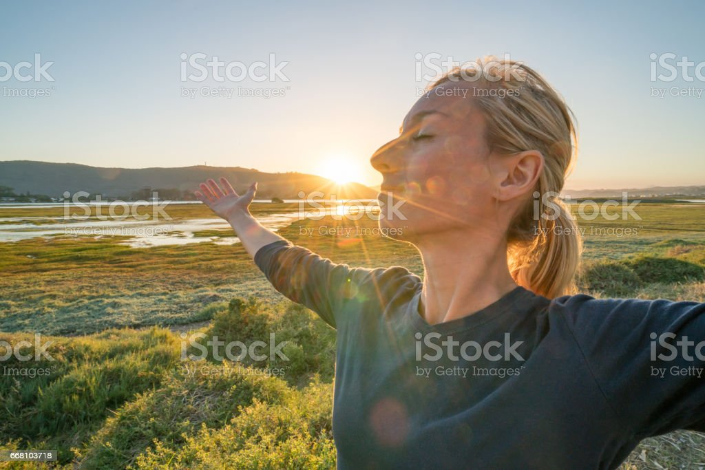 Young woman relaxing by the sea, arms outstretched stock photo