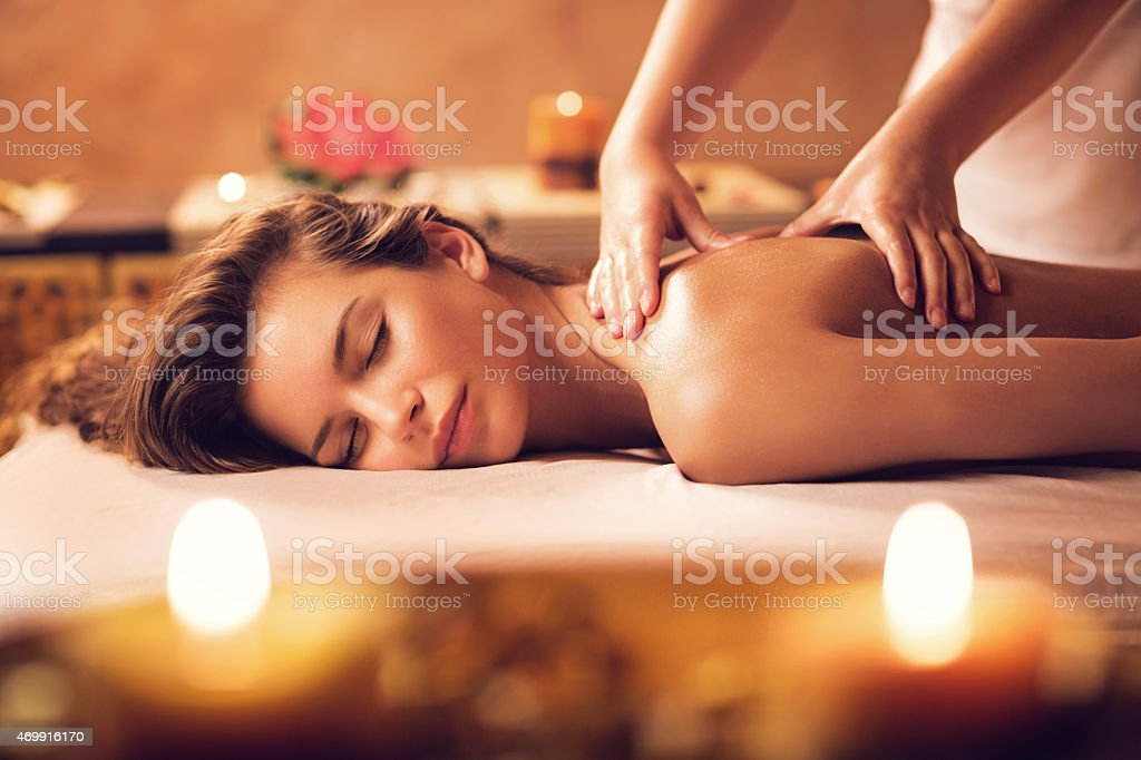 Young woman relaxing during back massage at the spa. stock photo