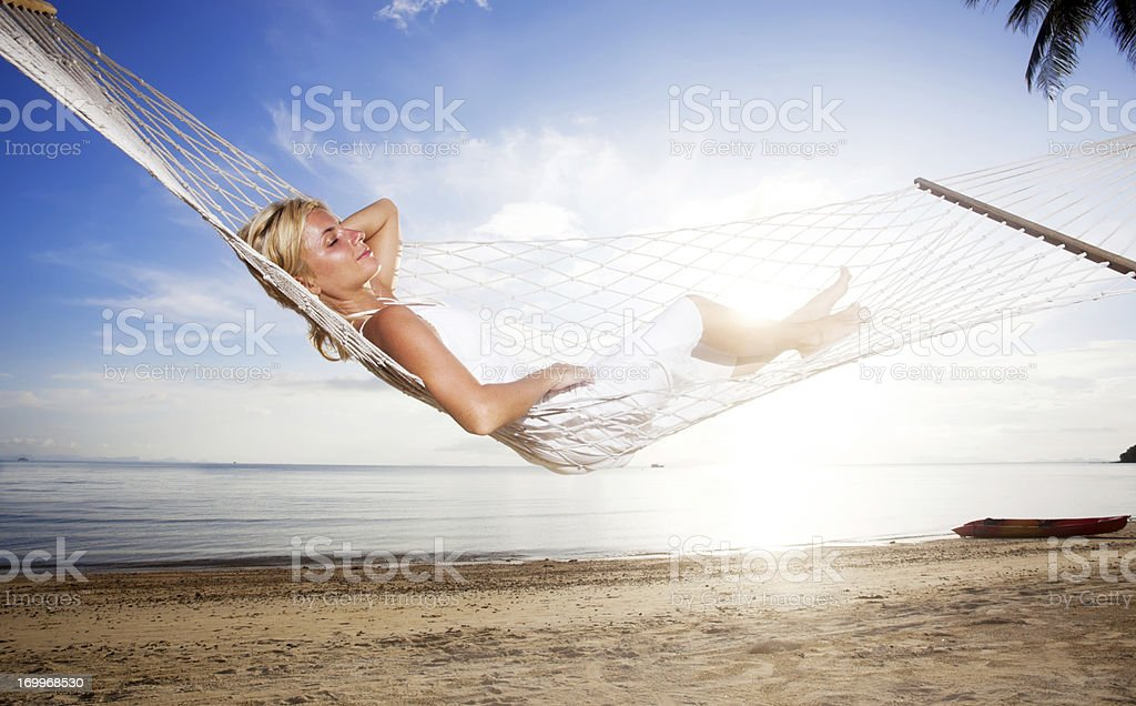 Young woman relaxing in a hammock at the tropical beach royalty-free stock photo