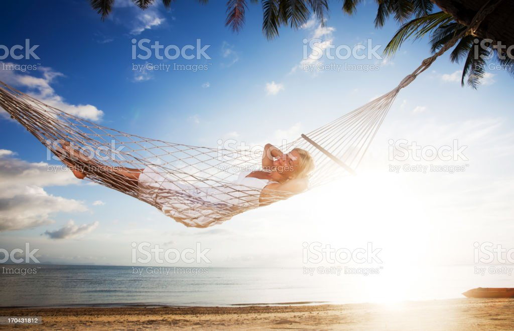 Young woman relaxing in a hammock at the tropical beach. royalty-free stock photo