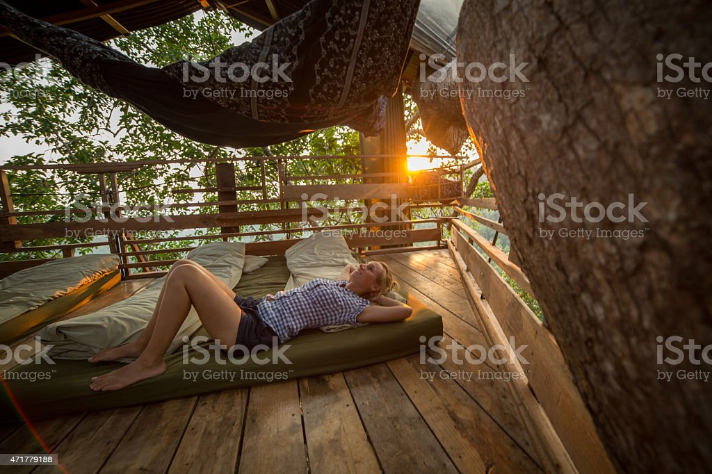 Young woman relaxing in a tree house at sunset stock photo