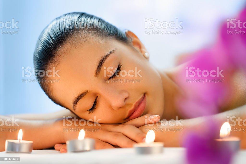Jeune femme de se détendre dans la lumière tamisée des bougies de signalisation après massage. photo libre de droits