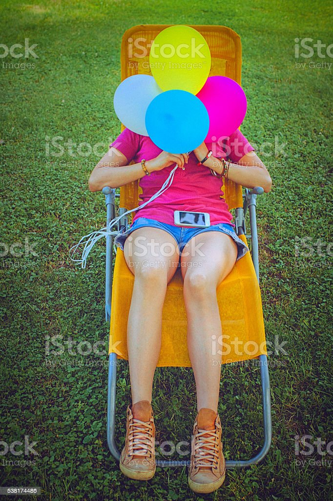 Young woman relaxing in easy chair in the garden stock photo