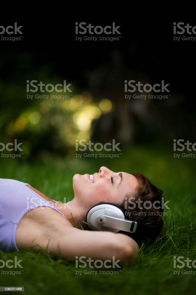 Young Woman Relaxing in Grass and Wearing Headphones royalty-free stock photo