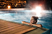 Young woman relaxing in heated swimming pool during winter night.