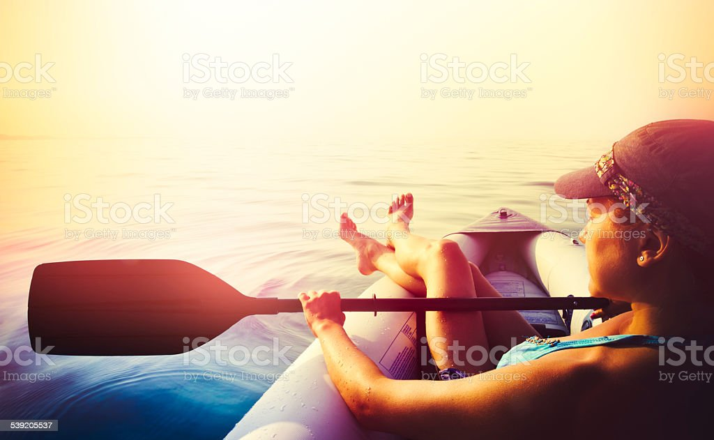 Young woman relaxing in kayak on sea at sunset stock photo
