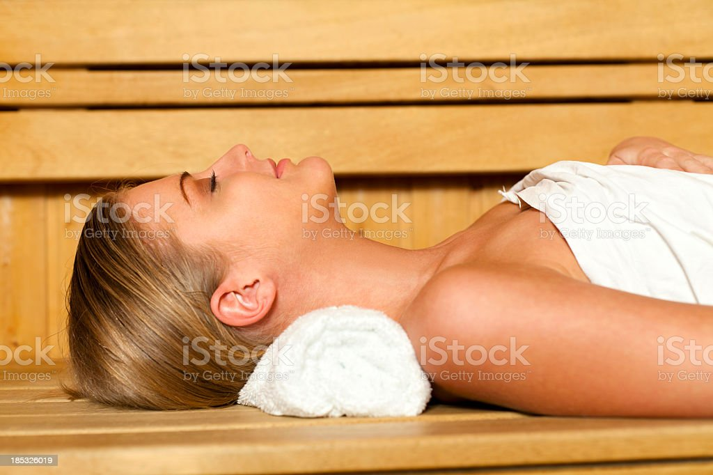 Young woman relaxing in sauna stock photo