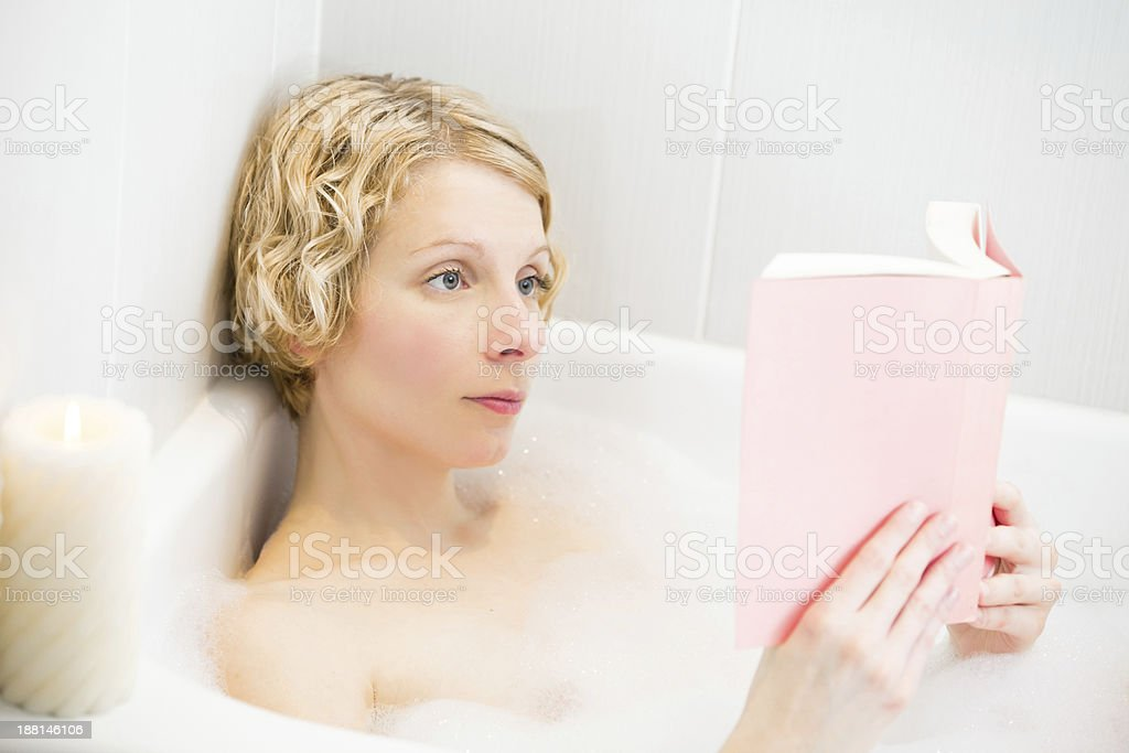 Young woman relaxing in the bath and reading a book royalty-free stock photo