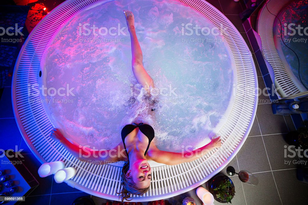 Young woman relaxing in the hot tub stock photo