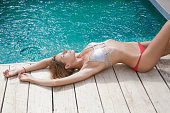 Young woman relaxing next to the pool
