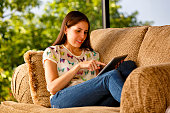 Young woman relaxing on a couch with tablet computer