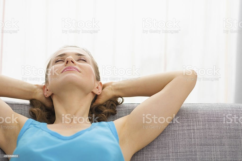 young woman relaxing on couch in living room stock photo