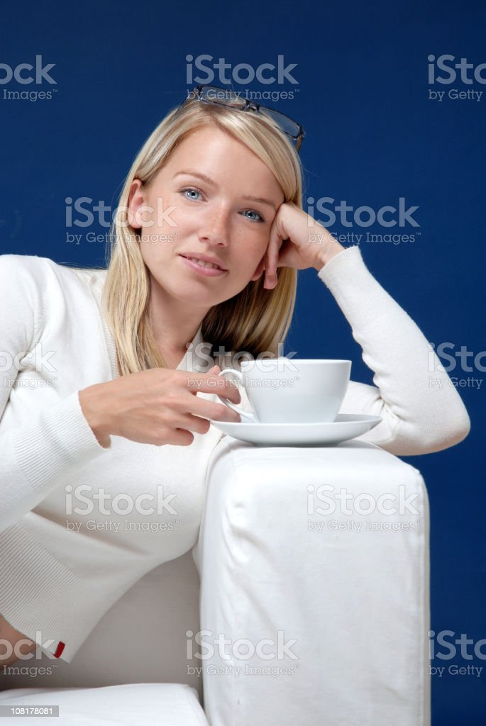 Young Woman Relaxing on Couch with Cup of Tea royalty-free stock photo