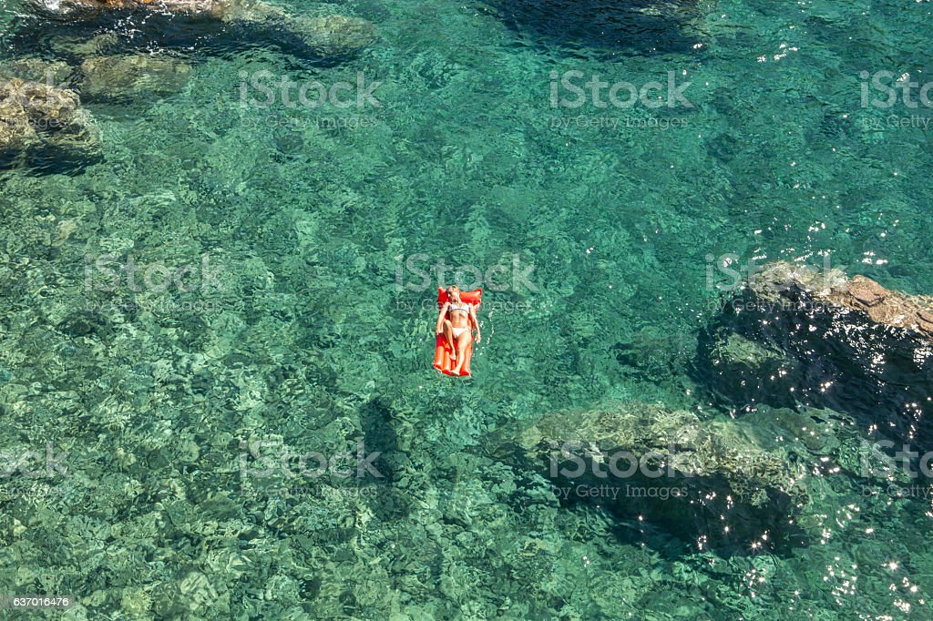 Young woman relaxing on floating mattress above sea stock photo