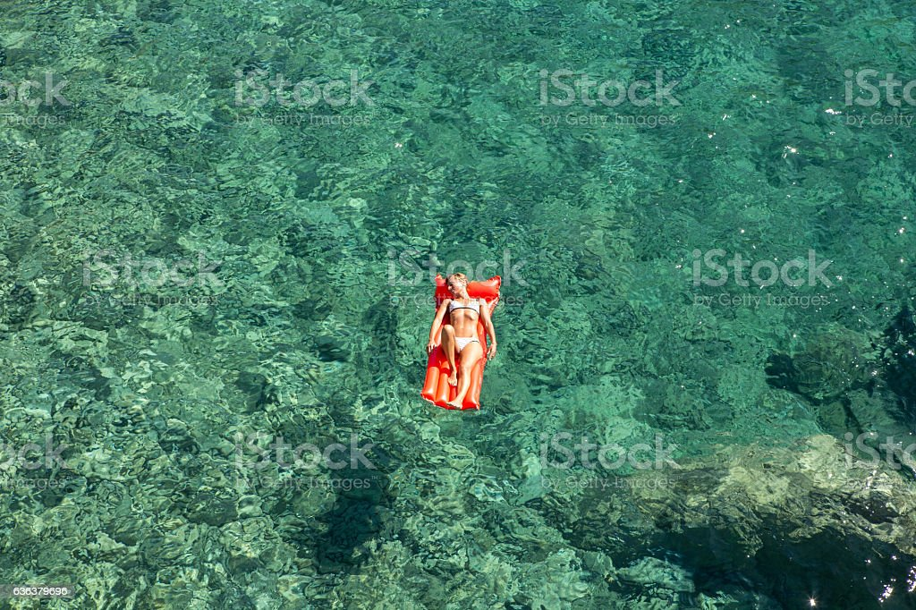 Young woman relaxing on floating mattress in cove-Italy stock photo
