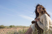 Young woman relaxing on grassy dune, low angle view