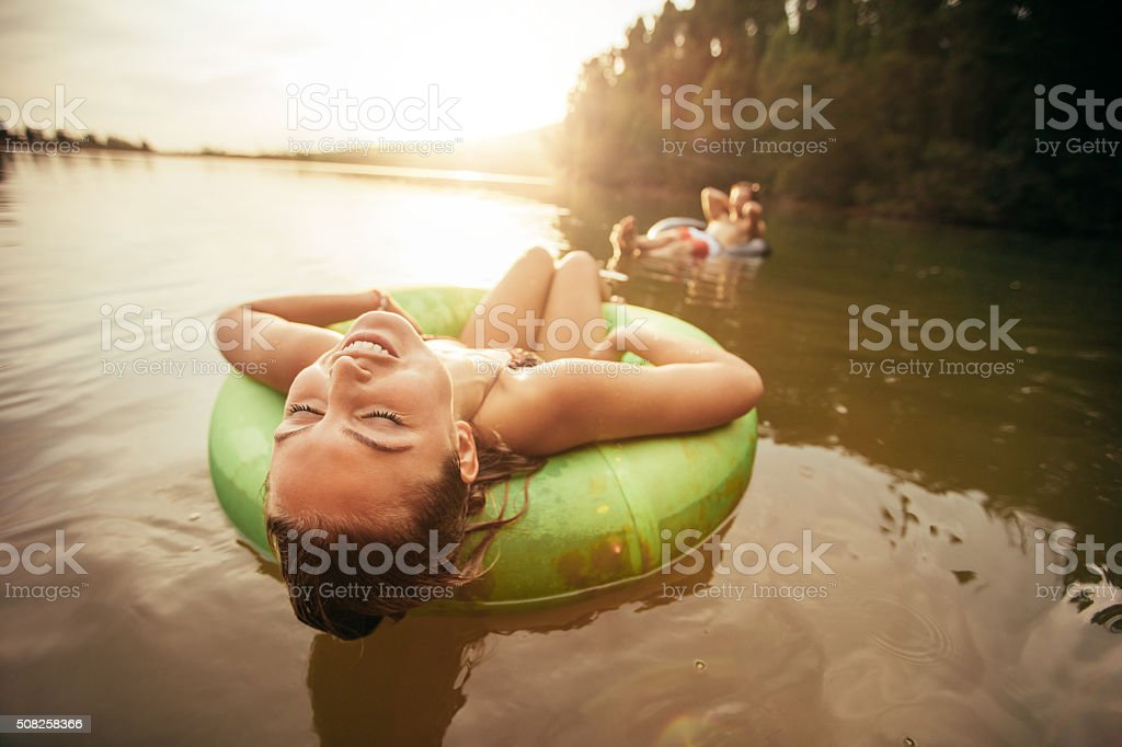 Young woman relaxing on inflatable ring in lake stock photo
