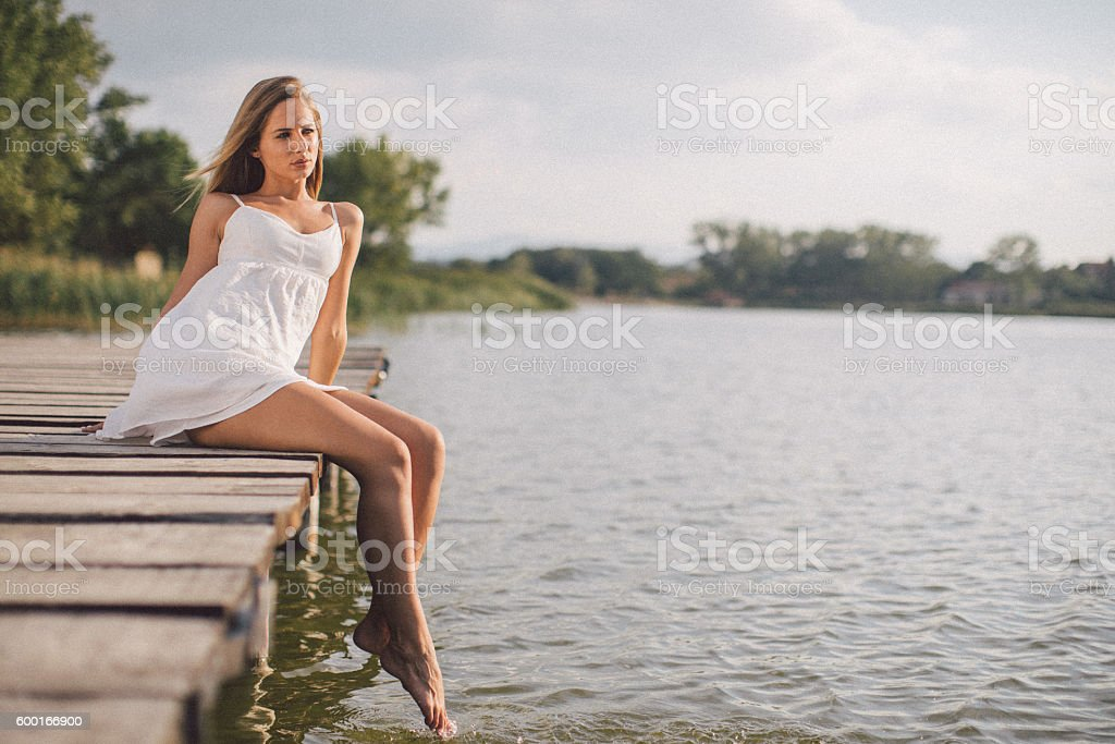 Young woman relaxing on jetty above lake stock photo