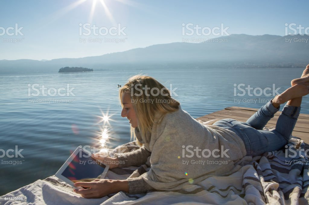 Young woman relaxing on lake pier with digital tablet – Foto