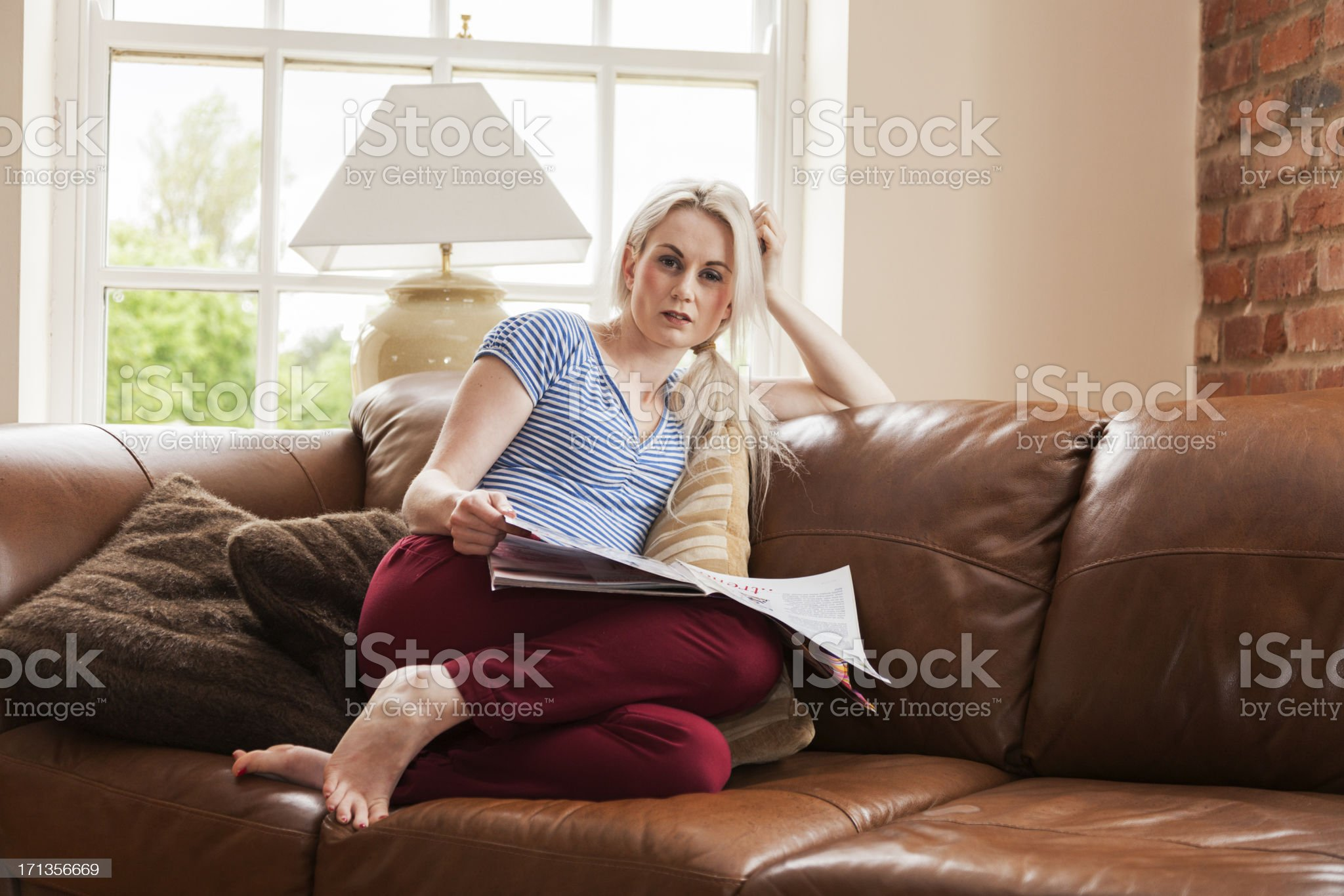 Young woman relaxing on sofa reading magazine. royalty-free stock photo