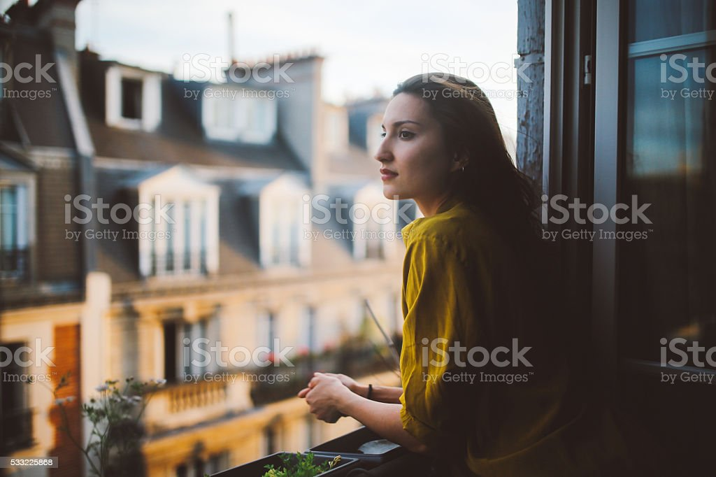 Young woman relaxing on the balcony of her Montmartre apartment stock photo