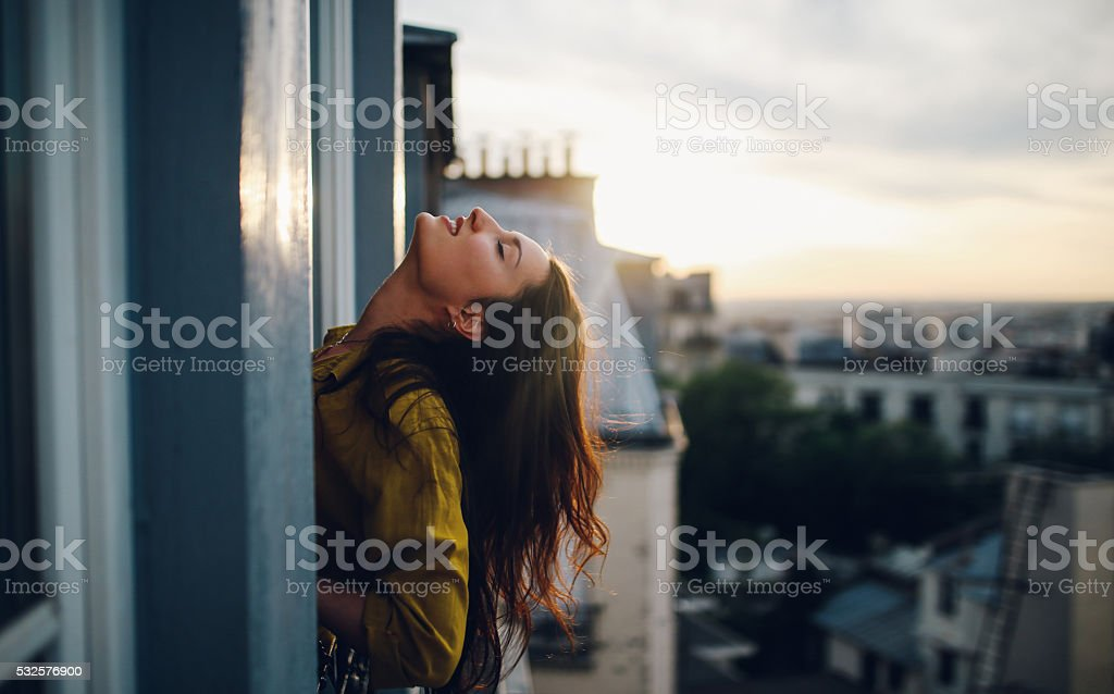 Young woman relaxing on the balcony of her Parisian apartment stock photo