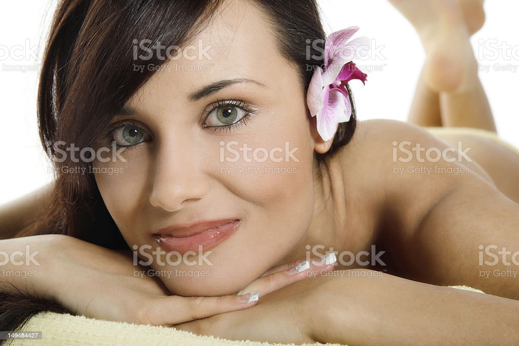 Young woman relaxing with flower and hot stones royalty-free stock photo
