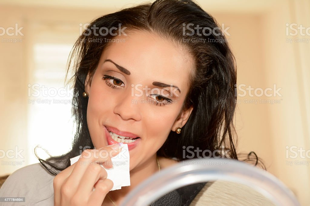 young woman removing lipstick stock photo