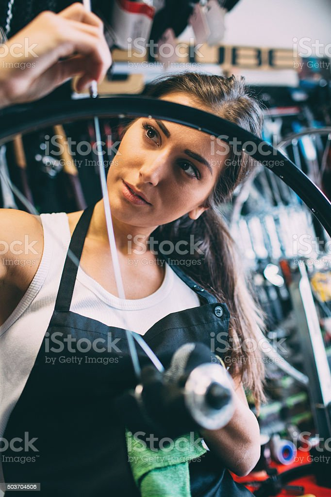 Young woman repairing a bike stock photo